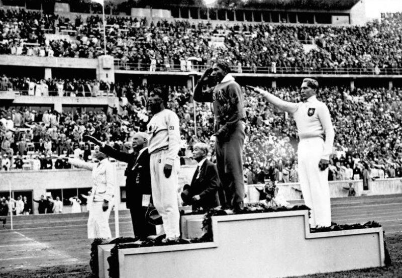 Jesse Owens en el podio olímpico después de su victoria en el salto de longitud en los Juegos Olímpicos de Berlín 1936 junto a Naoto Tajima (izquierda) y Luz Long (derecha).